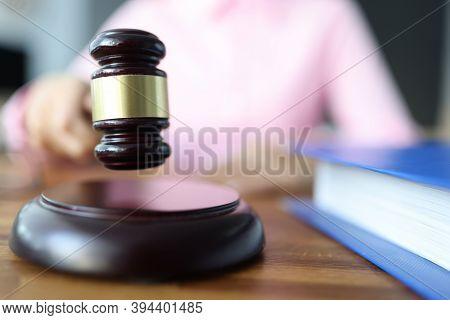 Female Hand Holds A Wooden Gavel For Judges. Civil Litigation Concept