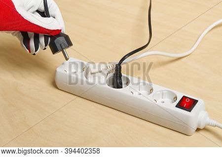 Closeup Of An Electrician Plugging Extension Cords Into Each Other. Mans Hand Plugging Extension Cor