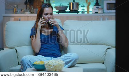 Woman In Pajamas Talking At Phone Watching Tv And Eating Snacks. Happy, Relaxed, Lonely Lady In Paja