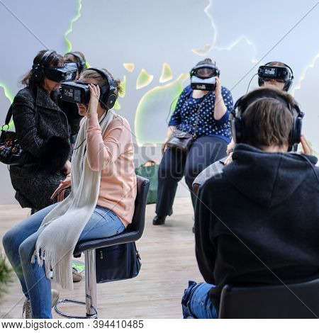 A Room With People Immersed In Virtual Reality. Oculus Rift Gear Vr Helmets. Exhibition Days Of The