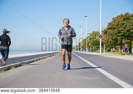 Focused Tired Mature Man In Sports Clothes Jogging Along River Bank Outside. Senior Jogger Training