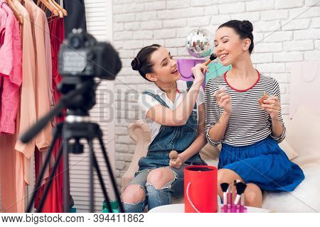 Two Fashion Blogger Girls Hold Up Brush And Perfume To Camera.