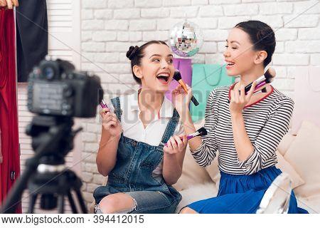 Two Fashion Blogger Girls Hold Up Many Brushes To Camera.