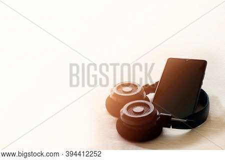 Smartphone And Headphone On Table Outdoor With Natural Sunlight Morning Background.