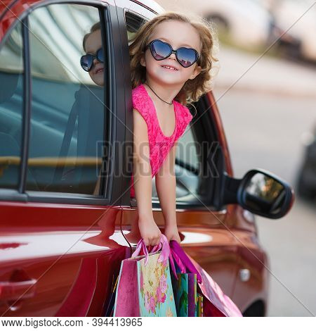 Beautiful Happy Smiling Little Girl Child In Sun Glasses Is Holding Shopping Bags Near Shopping Mall