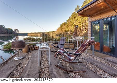 Rocking Chair On A Wooden Pier By The Lake. House On The Water. Resting Place Against The Backdrop O