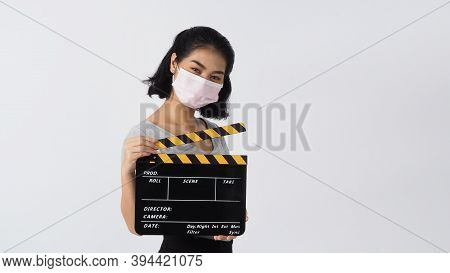Girl Or Woman Wear Face Mask And Hand's Holding Black Clapper Board Or Movie Slate Use In Video Prod
