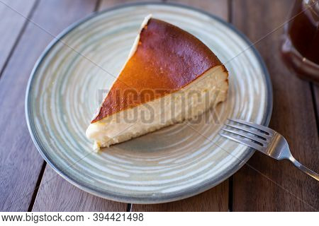 Cheescake San Sebastian Slice On Dish At Cafe Table