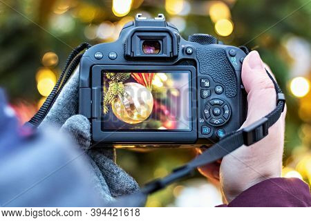 The Girl Takes Pictures Of The Christmas Lights With The Camera. Festive New Year's Night Streets