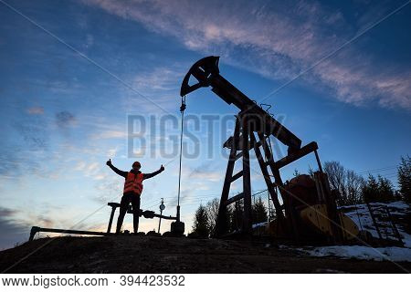 Low Angle View Snapshot Silhouette Of Oil Worker Standing Near The Oil Pump Jack With His Hands Up S