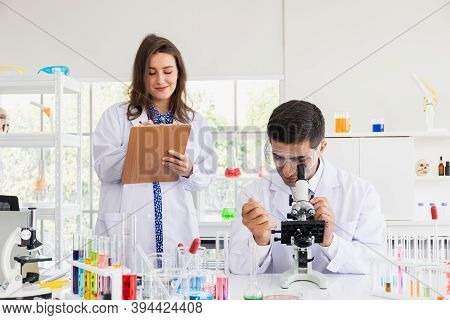 A Male And Female Scientist In A Science Laboratory. A Male Scientist Is Using A Microscope While A