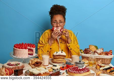 Gluttony And Overeating Concept. Upset Crying Ethnic Woman Eats Piece Of Cake Reluctantly, Sits At T
