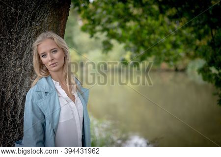 Smiling Young Woman Leaning On A Tree By The Side Of A River