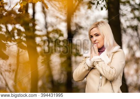 Attractive Young Woman Is Praying In The Park Hoping For Better Times To Come. Concept For Faith, Sp