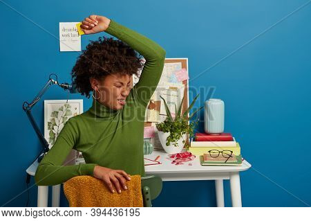 Displeased Curly Woman Smells Unpleasant Stinch Under Armpit, Wears Green Turtleneck, Sits Over Cowo