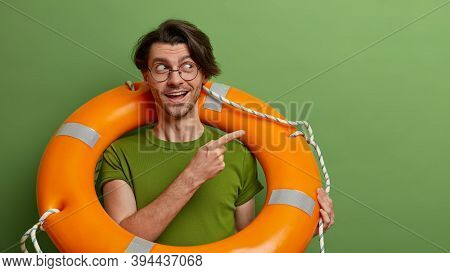 Positive Lifesaver With Inflated Lifebuoy Points Aside And Shows Way To Sea, Ready For Assistance An