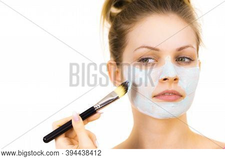Young Woman Applying With Brush Green Mud Mask To Face, On White. Teen Girl Taking Care Of Oily Skin