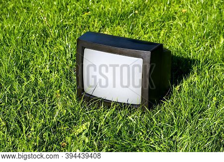 Old Analog Television Set On The Grass Outdoor