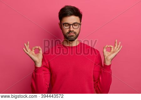 Peaceful Bearded Man Practices Yoga, Meditates With Zen Gesture, Closes Eyes, Expresses Calmness And