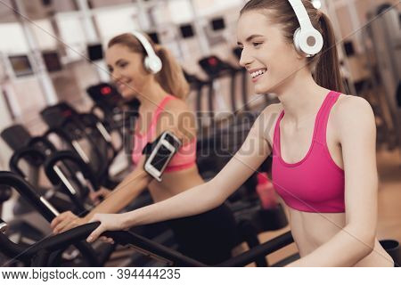 Mother And Daughter Running On Treadmill At The Gym. They Look Happy, Fashionable And Fit.