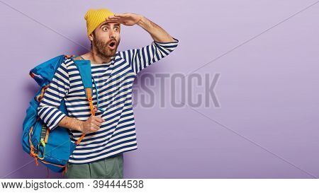 Shocked Male Backpacker Carries Tourist Rucksack, Enjoys Journey Alone, Wears Yellow Hat And Striped