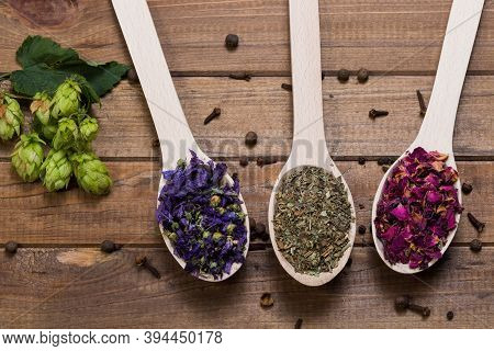Dried Myosotis Mallow Flower Herbal Tea, Green Tea And Rose Flowers On Spoons On Wooden Table