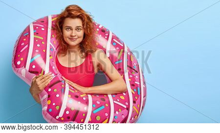 Pleased Redhead Woman Wears Red Bathing Suit, Stands Into Swimring, Has Pleased Face Expression, Spe