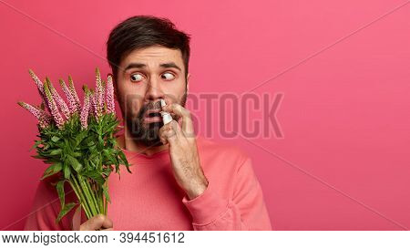 Photo Of Unhealthy Man Cant Breath Well, Has Allegy On Seasonal Plant, Sprays Nose With Nasal Drops,
