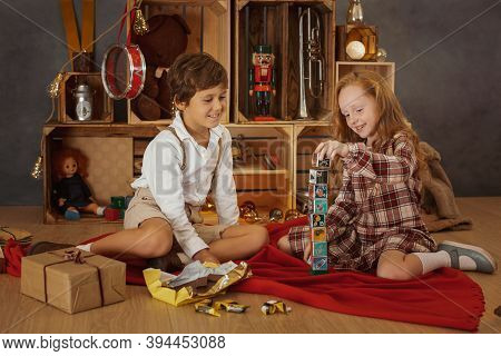 Happy Holidays Concept. Two Kids Playing With Blocks On The Floor, A Creative Christmas Tree Made Fr