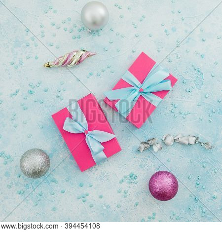 Christmas Concept Of Pink Gift Box And Decoration On Blue Background. Winter Holiday Composition. Fl