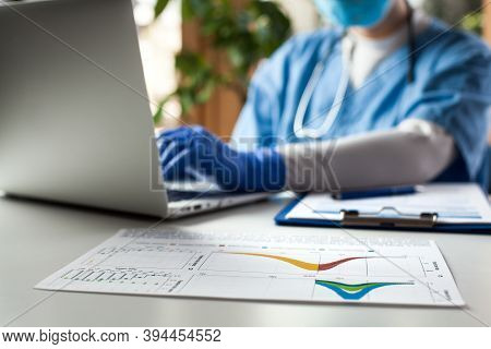 Epidemiologist Doctor Working On Laptop Computer,analyzing Graphs & Charts,covid-19 Coronavirus Glob