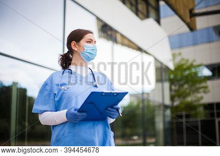 Young Female Caucasian Uk Nhs Doctor Looking In Distance With Fear Worry Anxiety & Uncertainty In Ey