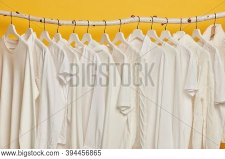 Same White Clothes On Wooden Racks In Closet. Collection Of Clothing On Hangers, Isolated Over Yello