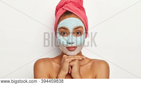 Headshot Of Attractive African American Woman Applies Natural Facial Mask, Wears Pink Towel On Head,