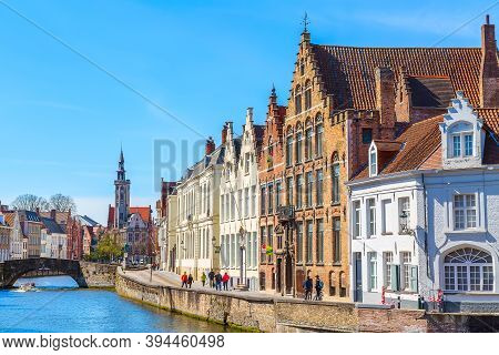Bruges, Belgium - April 10, 2016: Panorama With Canal, Cathedral Tower And Colorful Traditional Hous