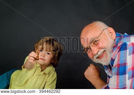 Chess Game. Kid Playing Chess With Grandpa. Grandfather Teaching Grandson Play Chess. Family Relatio