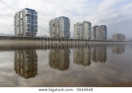 Coastal City Reflected In The Beach