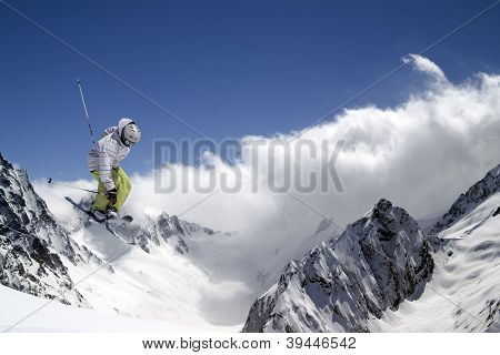 Freestyle ski jumper with crossed skis against blue sky and snow mountains poster