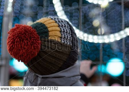 Back View Of Boy Looking At Christmas Tree And Christmas Decorations.