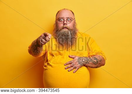 Stunned Shocked Bearded Obese Man Points Index Finger At Camera And Holds Tummy, Reacts To Overwhelm