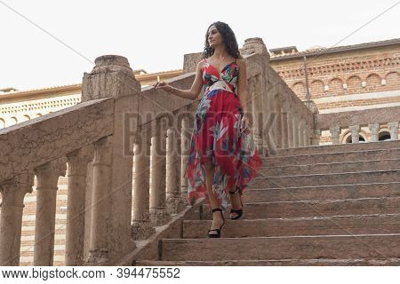 Young Curly Girl With Colorful Summer Dress. Walks Around The City By Day, Background Of An Ancient
