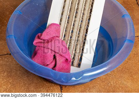 Apartment Cleaning: Rag And Dusty Ventilation Grill In A Basin Of Water On The Floor