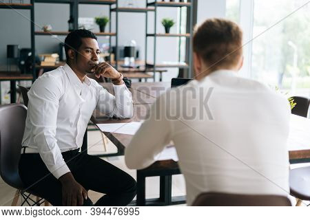 Pensive Serious Professional African American Man Interviewing Caucasian European Young Candidate Fo