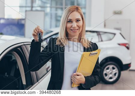 Mature Female Car Dealer Smiling To The Camera Cheerfully, Holding Car Keys, Standing In Front Of A