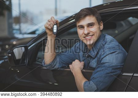 Excited Young Man Smiling Holding Car Keys, Sitting In A New Automobile At The Dealership. Happy Man