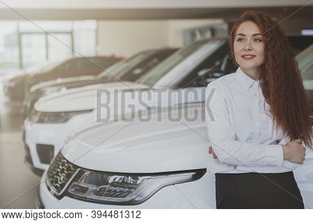 Long Haired Beautiful Young Businesswoman Looking Away Thoughtfully, Leaning On A New Car At The Dea