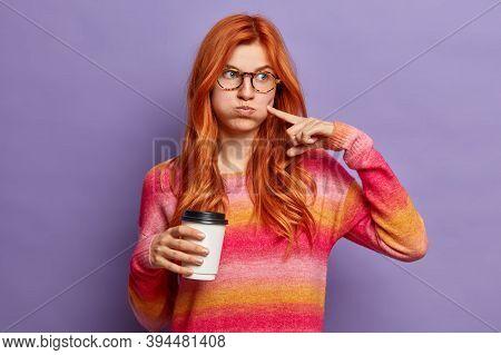 Pensive Redhead Woman Blows Cheeks And Lips, Drinks Take Away Coffee. Pretty Ginger European Girl We