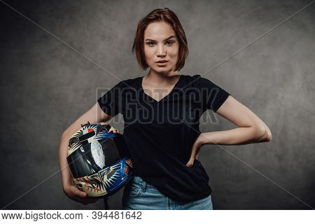 Glamour And Self Confident Female Motorcyclist In Black Shirt With Short Haircut Poses Holding Helme