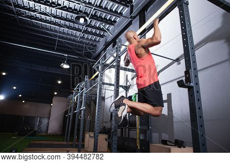 Low Angle Rear View Shot Of A Muscular African Male Athlete Doing Pull Ups At The Gym, Copy Space. S