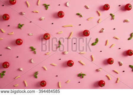 Penne Macaron And Various Ingredients On Pink Background. Pasta, Tomatoes, Garlic, Peppercorns On Ro